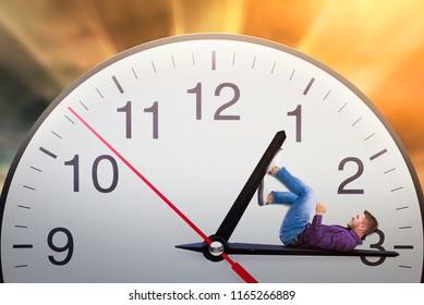 Man lies on the arrow of a huge clock