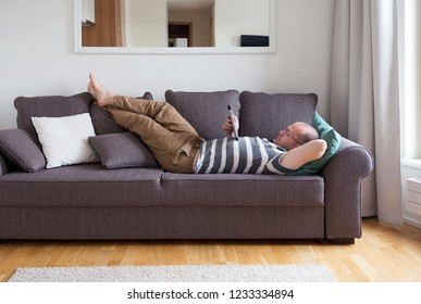 man lies on the couch and using a digital tablet
