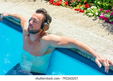 Man lies on the edge of a swimming pool and relaxes while listening to music