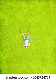 A man lies on a green lawn and smiles with happiness. Top and aerial view with copy space. Minimal styled flat lay isolated on original green grass background. He depicts an angel from the grass
