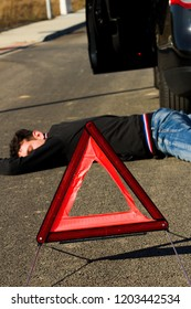 The man lies on the road behind the black car and warning triangle.The car collided pedestrian was on the ground.
