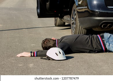 The man lies on the road behind the black car next to the bicycle helmet.The car collided pedestrian was on the ground.