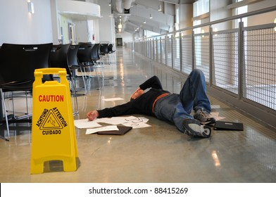Man lies on the wet floor on which he slipped in spite of caution sign, selective focus on man's head