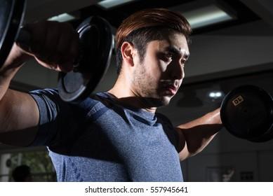Man lift weight on shoulder press with studio light shot