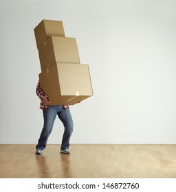 Man lifting cardboard boxes in apartment interior