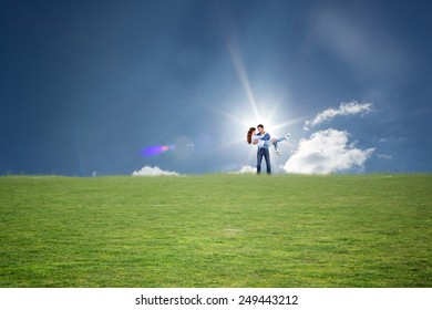 Man lifting up his girlfriend against cloudy sky with sunshine