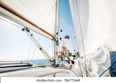 man lifting the sale of yacht boat during regatta
