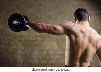 Man lifting weights, back image at old gym.