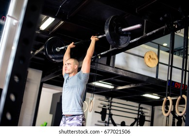 Man is lifting weights over his head in gym