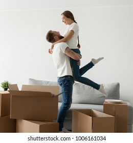 Man lifting woman standing among boxes happy to move into new house, husband holding embracing wife celebrating buying own home, boyfriend and girlfriend enjoying moving day, starting living together