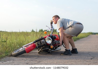 A man lifts a heavy motorcycle that fell after an accident