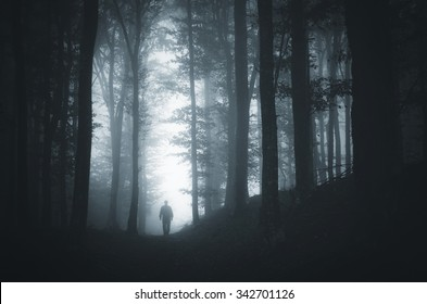 man in light spot in dark forest