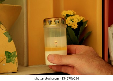 Man lighting a candle in a columbarium of a crematorium