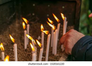 man lighting candles for praying