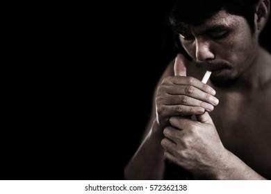 man lighting cigarette on black