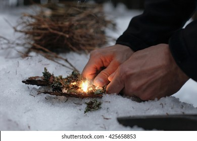 Man lighting a fire in a dark winter forest, preparing for an overnight sleep in nature, warming himself with DIY fire. Adventure, scouting, survival concept.