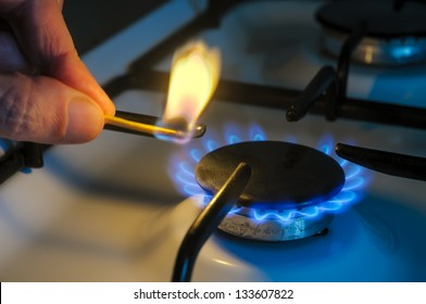 A man lighting the gas-stove with a match