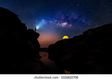 the man lighting his flashlight to sky deposit of yellow tent at the top of rock hill with milky way and stars background