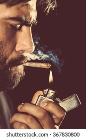 Man lighting his joint and smoking it with pleasure