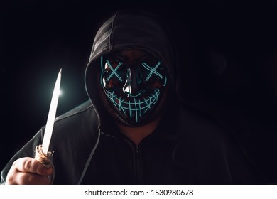 Man with lighting neon glow mask in hood and big knife in hand on black background. Halloween and horror concept