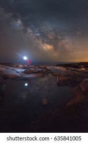 Man lighting up a tide pool under the Milky Way Galaxy