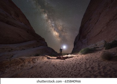 Man lighting up the White Domes in Nevada as the Milky Way Galaxy rises