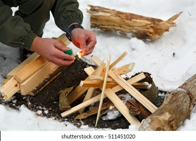 A man lights a match to make a fire in winter forest.