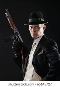 Man like a chicago gangster in suit and light waistcoat  with submachine gun