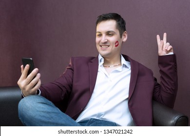 A man with lipstick on a cheek kiss. Young playboy lover with lipstick makes a photo on a smartphone.