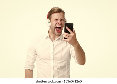 Man listen music earphones. Listen music radio with portable gadget. Guy shouting face concentrated on remembering song lyrics. Remember lyrics. Read lyrics smartphone screen. Sing smartphone karaoke.