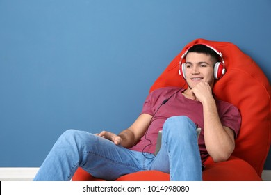 Man listening to audiobook through headphones near color wall