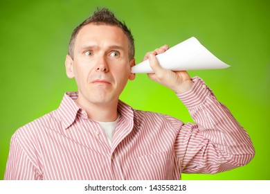 Man listening with eartrumpet made of paper, could be a concept for eavesdropping, secrecy or curiosity