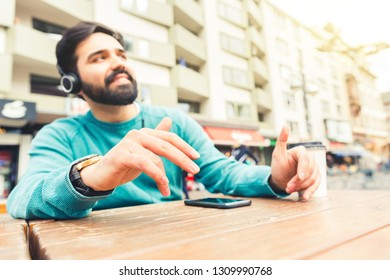 Man listening to music with headphones and dancing with hands. Young man sitting at a table in the city, keeping the rithm with his hands. Lifestyle and relax concepts