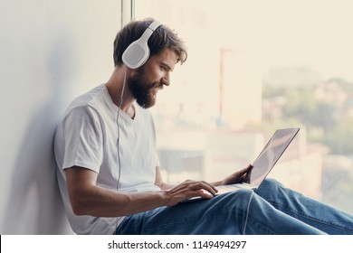 A man is listening to music from a laptop in headphones.