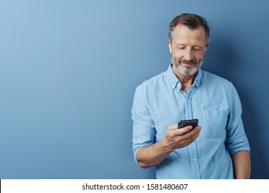 Man listening to music or media on his mobile phone using an ear bud posing over a blue studio background with copy space