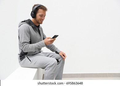 Man listening to music mobile phone app wearing headphones sitting at home. Healthy lifestyle sport athlete using smartphone on jogging break outdoors.