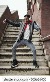 Man listening to music standing on stairs and performing a dance.