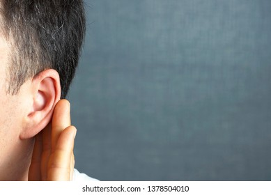 The man listens attentively with her palm to her ear, close up, the news concept