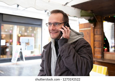 A man listnens good news on the phone and smiles - front view