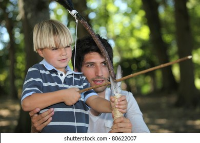 a man and a little boy doing archery in the forest