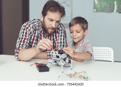 The man and the little boy measure the robot's performance. They use a digital multimeter. The boy observes with delight the work of a man