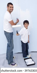 Man and little boy painting a wall at home