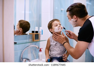 Man and little boy with shaving foam on their faces looking into the bathroom mirror and laughing. Father and son having fun while shaving in bathroom.