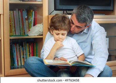 man and little boy sitting on the floor in living room and reading book