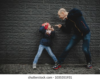 Man and little girl play outside on the street