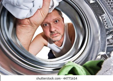 Man loading cloths to washing machine. View from inside the washing machine.