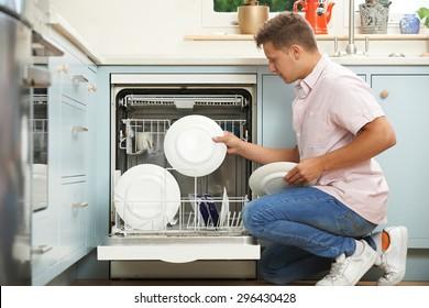 Man Loading Dishwasher In Kitchen