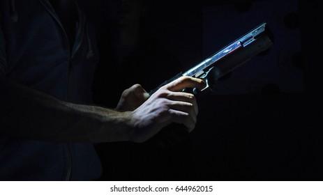 Man Loading A Gun In The Dark