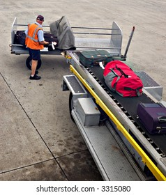 A man is loading luggage onto airplane