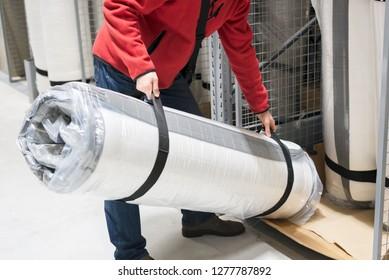 Man loading roll of mattress in warehouse